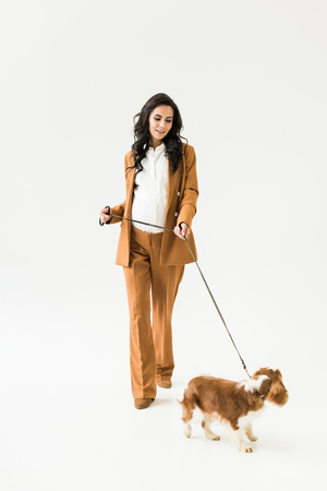 Curly pregnant woman in suit walking with dog on white background
