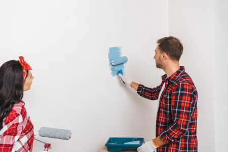 man painting wall in blue color near woman holding roller