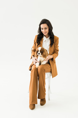 Smiling young woman in brown suit sitting on chair and holding dog on white background Stock Photo