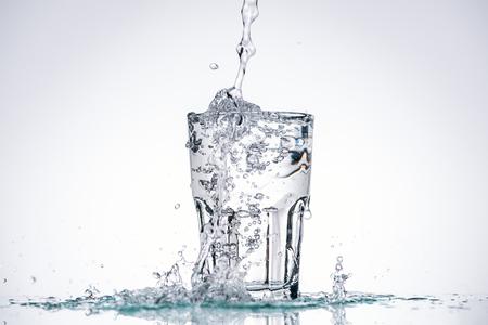acqua che versa nel bicchiere pieno su sfondo bianco con retroilluminazione e schizzi Archivio Fotografico