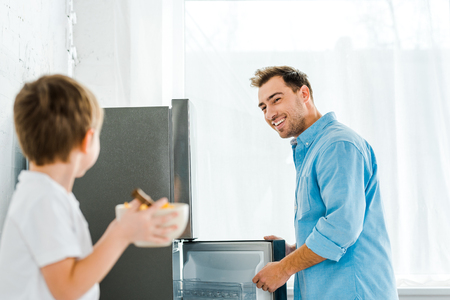 selective focus of smiling father in kitchen with boy holding bowl of cereal on foreground