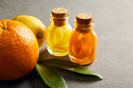 Glass bottles of essential oil with orange and lemon on dark surface