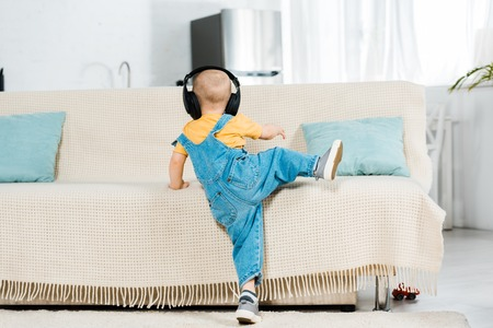 back view of male toddler in headphones listening music and climbing on couch at home