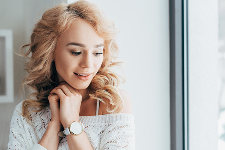 Charming curly young woman in white sweater and wristwatch looking down