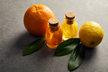 Bottles of essential oil with orange and lemon on dark surface