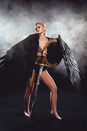 beautiful woman in warrior costume and angel wings posing with shield and sword on black background