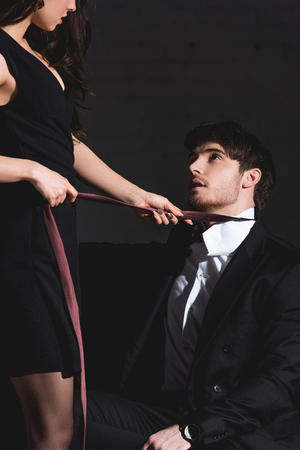 brunette woman in black dress taking off burgundy tie with handsome man in suit sitting on couch on black background