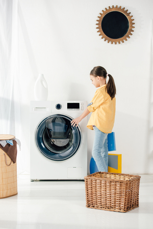 side view of child in yellow shirt near basket opening washer in laundry room