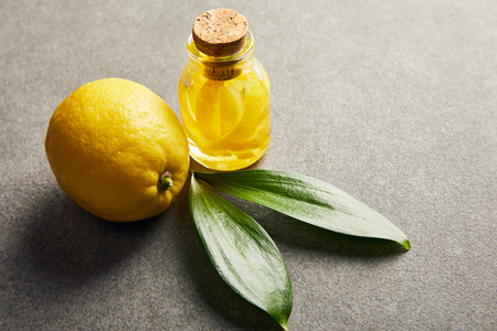 Whole lemon and glass bottle with essential oil on dark surface