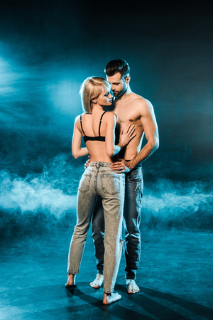 beautiful seductive couple embracing on blue smoky background 版權商用圖片