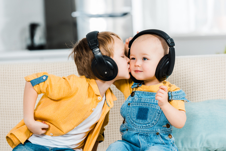 adorable preschooler boy in headphones kissing brother on cheek at home