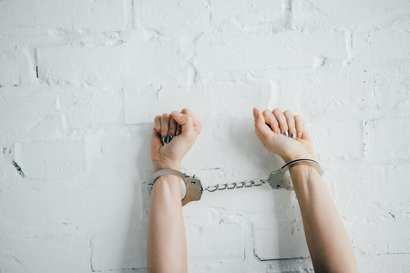 cropped view of woman with handcuffed hands near brick wall