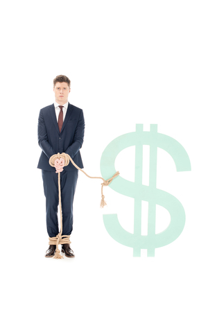 professional businessman bound with rope to dollar sign isolated on white Reklamní fotografie