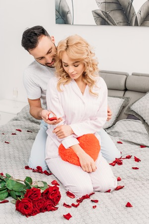 Handsome man sitting on bed with roses and proposing to attractive woman