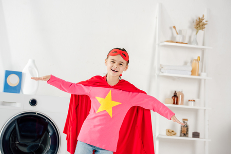 child in red homemade suit with star sign having fun in laundry room
