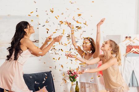 beautiful multicultural girls in nightwear having fun under falling confetti during pajama party