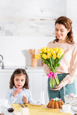 Mother holding tulips bouquet and looking at daughter near easter table
