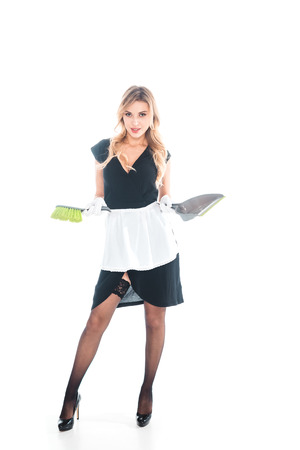 attractive housemaid in black uniform, apron, stockings standing with broom and   scoop on white background Stock Photo