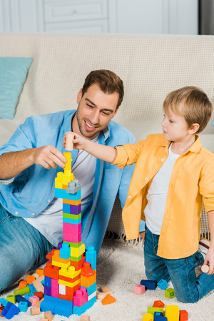 smiling father and preschooler son playing with colorful building blocks at home