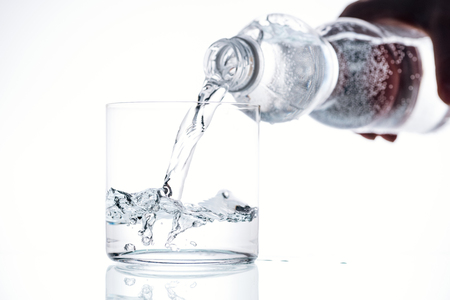 cropped view of man pouring water from plastic bottle in glass on white background Stok Fotoğraf - 119000725