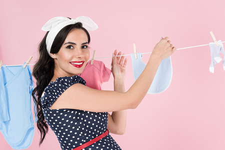 Charming pregnant woman hanging out baby clothes with smile isolated on pink