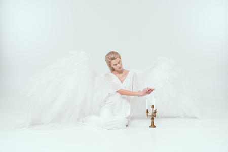 beautiful woman in angel costume with wings sitting near candelabrum with candles isolated on white