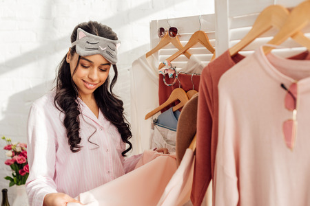 beautiful smiling african american girl in sleeping mask choosing clothes in bedroom wardrobe