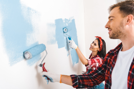 happy couple painting wall in blue color at home Standard-Bild - 118999362