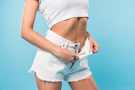 Cropped view of slim girl in crop top taking off shorts on blue background 版權商用圖片