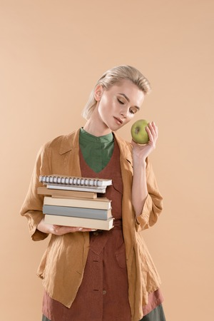 attractive young woman holding books and green apple while standing in eco clothing isolated on beige