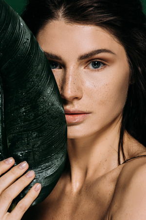 beautiful woman with freckles posing with green tropical leaf