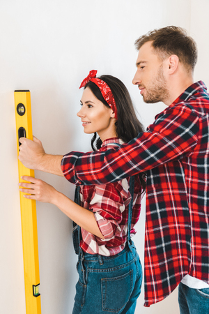 happy couple holding measuring level near wall at home Standard-Bild - 118998991
