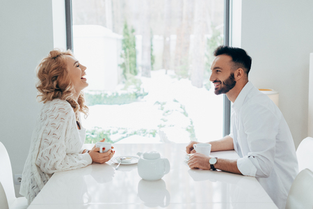 Blissful couple laughing while drinking coffee together