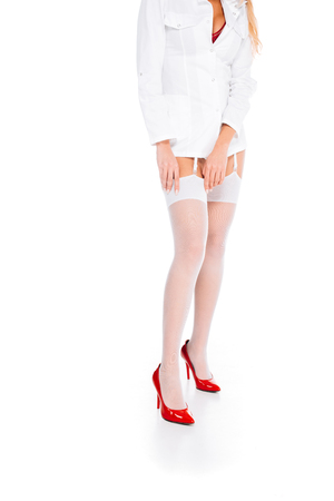 cropped view of nurse in short coat and red shoes correcting stockings on white background