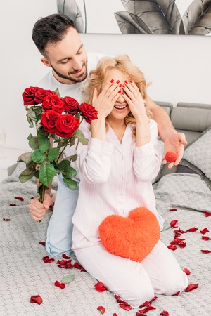 Man making proposal and presenting flowers to girlfriend in bedroom
