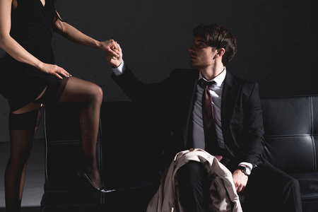 handsome man sitting on couch wile woman in black dress and stockings putting leg on sofa on dark background Stockfoto