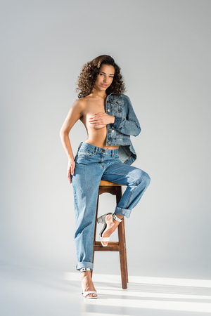 Attractive girl in jeans sitting on chair and covering breast with hand on grey background 版權商用圖片