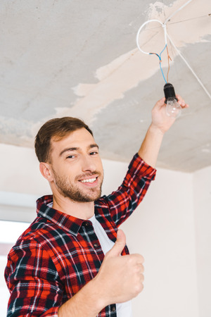 cheerful man changing light bulb and showing thumb up Standard-Bild - 118997775