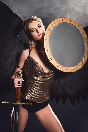 beautiful woman in warrior costume and angel wings posing with shield and sword on dark background