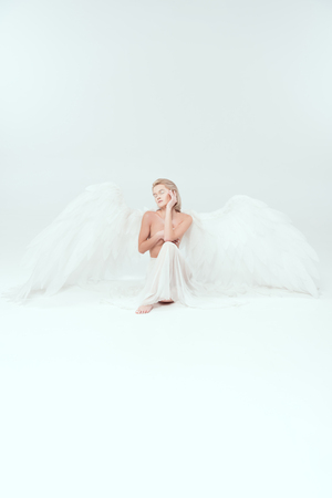 beautiful woman with angel wings covering breasts and posing isolated on white with copy space Stock Photo