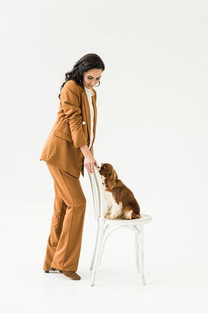 Beautiful pregnant woman in suit looking at dog on chair on white background