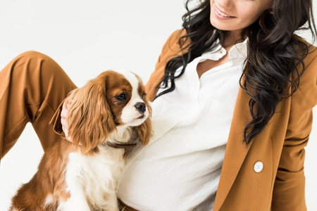 Partial view of pregnant woman in brown jacket stroking dog isolated on white