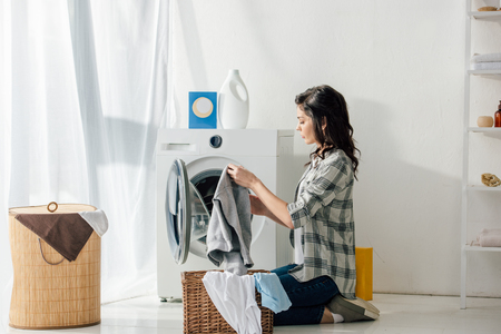 woman in grey shirt and jeans putting clothes in basket near washer in laundry room