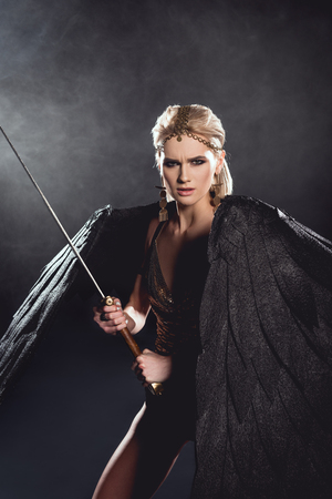 beautiful aggressive woman in warrior costume with angel wings holding sword and looking at camera on black background