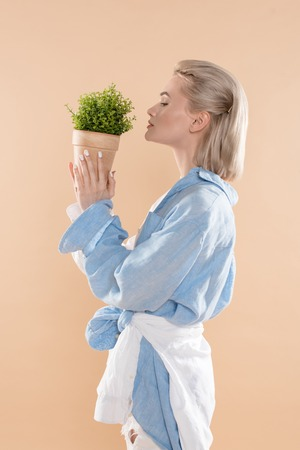 profile of woman holding pot with plant and standing in eco clothing isolated on beige, environmental saving concept