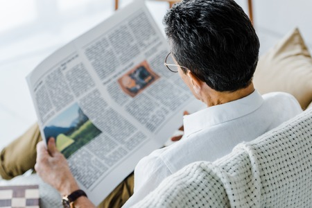 selective focus of man reading newspaper at home 写真素材