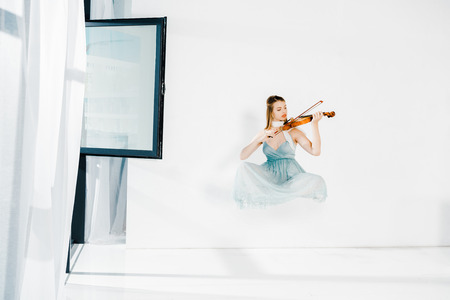 floating girl in blue dess playing violin on white background Banco de Imagens