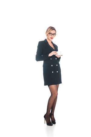 businesswoman in black formal wear with open neckline and high heels shoes drinking from cup on white background