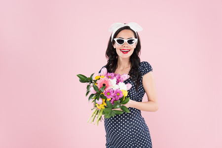 Charming pregnant woman in sunglasses holding flower bouquet isolated on pink