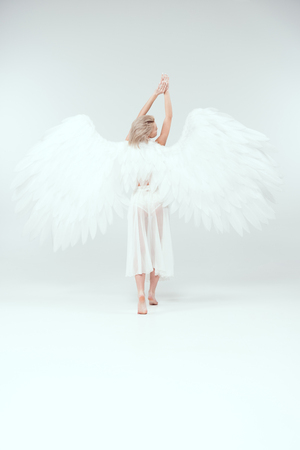 back view of woman with angel wings posing on white background